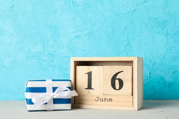 Houten kubussen kalenderdatum 16 juni en geschenkdoos op witte tafel tegen een achtergrond met kleur, ruimte voor tekst