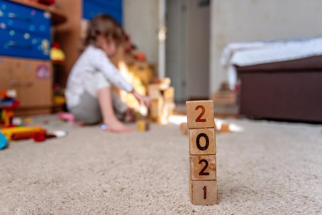 Houten kubussen met 2021 nummers staan op een rij klein kind bouwt een toren