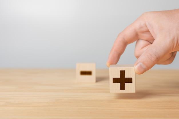 Houten kubussen met de afbeelding voors versus tegens plus of min zakenman houdt een kubus vast met plus-pictogram