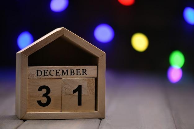 Houten kubussen met de cijfers 31 december en bokeh lichten