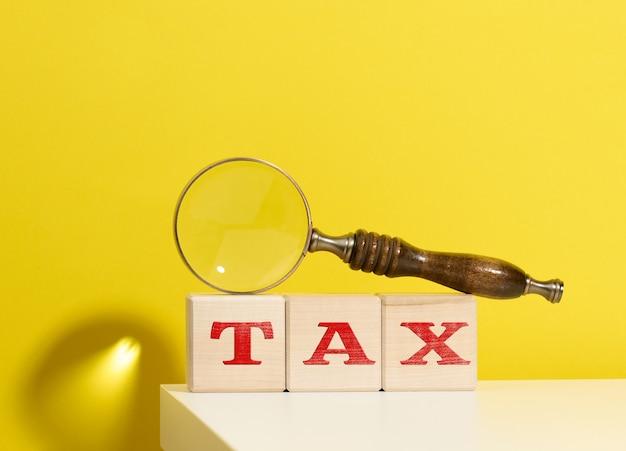 Houten kubussen met de inscriptie belasting en een bruin vergrootglas op een gele achtergrond