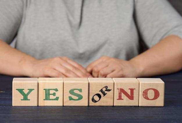 Houten kubussen met de inscriptie ja en nee op een nlue achtergrond. het concept van het analyseren en kiezen van de juiste beslissing, stemmen. waarheid of leugen