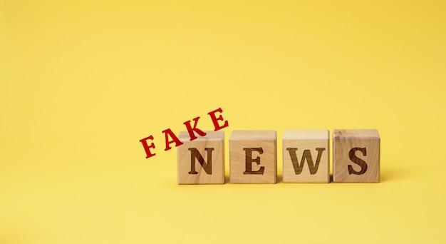 Houten kubussen met de inscriptie vals nieuws op een gele ondergrond