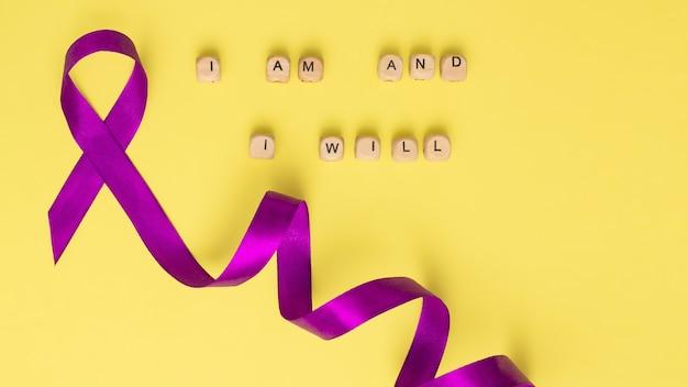 Houten kubussen met de tekst van de slogan van wereldkankerdag i am and i will en een paars lint, op een gele ondergrond. plat leggen