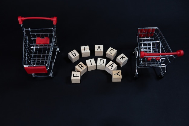 Houten kubussen met het opschrift black friday tussen twee supermarktwagens