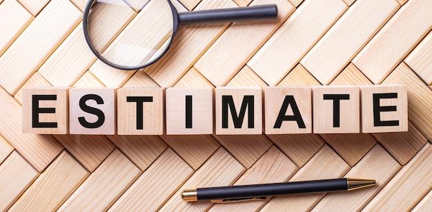 Houten kubussen met het woord estimate staan op een houten ondergrond tussen een vergrootglas en een pen