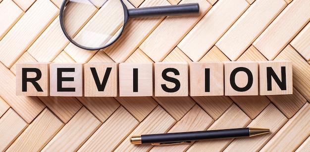 Houten kubussen met het woord revision staan op een houten ondergrond tussen een vergrootglas en een pen