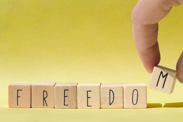 Houten kubussen met het woord vrijheid, vrijheid concept achtergrond close-up