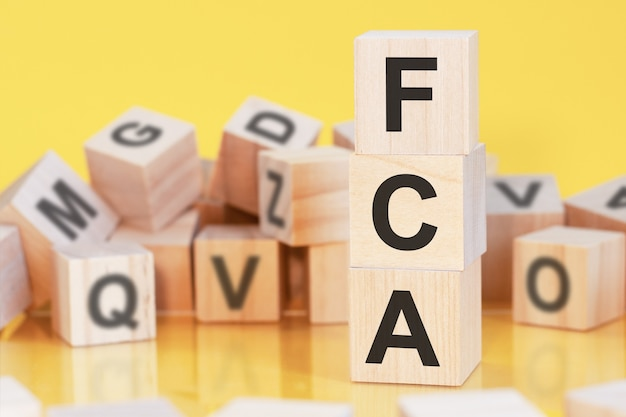 Houten kubussen met letters fca gerangschikt in een verticale piramide, gele achtergrond, reflectie van het oppervlak van de tafel, bedrijfsconcept, fca - afkorting van free carrier