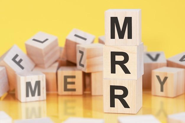 Houten kubussen met letters mrr gerangschikt in een verticale piramide, gele achtergrond, reflectie van het oppervlak van de tafel, bedrijfsconcept, mrr - kort voor monthly recurring revenue