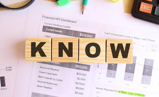 Houten kubussen met letters op de tafel in het kantoor. tekst know. financieel concept.