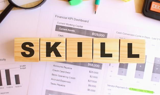 Houten kubussen met letters op de tafel in het kantoor. tekst skill. financieel concept.