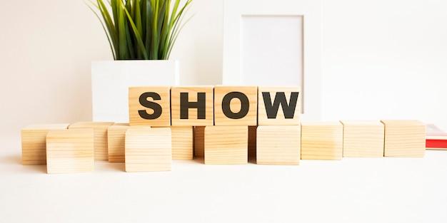 Houten kubussen met letters op een witte tafel. het woord is show. wit oppervlak met fotolijst en kamerplant