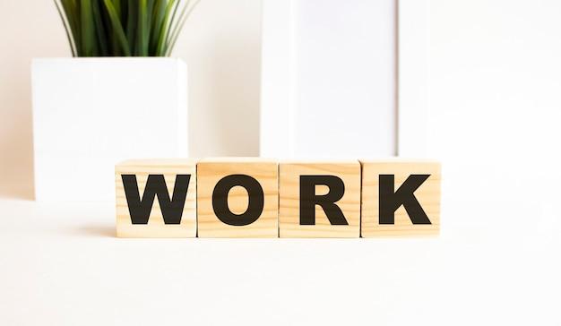 Houten kubussen met letters op een witte tafel. het woord is werk. witte achtergrond met fotolijst, kamerplant.