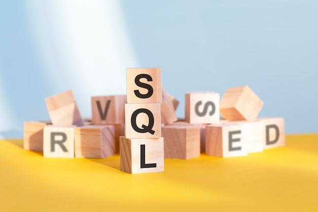 Houten kubussen met letters sql gerangschikt in een verticale piramide, grijze en gele achtergrond, bedrijfsconcept. sql - afkorting voor gestructureerde querytaal