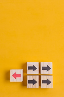 Houten kubussen met pijl op gele exemplaar ruimteachtergrond