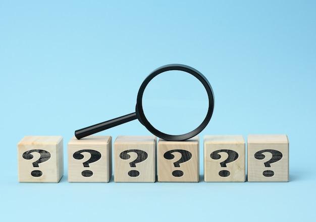Houten kubussen met vraagtekens en een vergrootglas op een blauwe achtergrond. het concept van het vinden van antwoorden op onbekende vragen, het oplossen van een probleem. informatie vinden