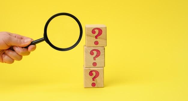 Houten kubussen met vraagtekens en een vrouwelijke hand houdt een vergrootglas op een geel oppervlak
