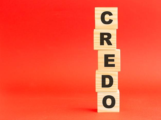 Houten kubussen met woord credo. houten kubussen op een rode ondergrond. vrije ruimte aan de linkerkant.