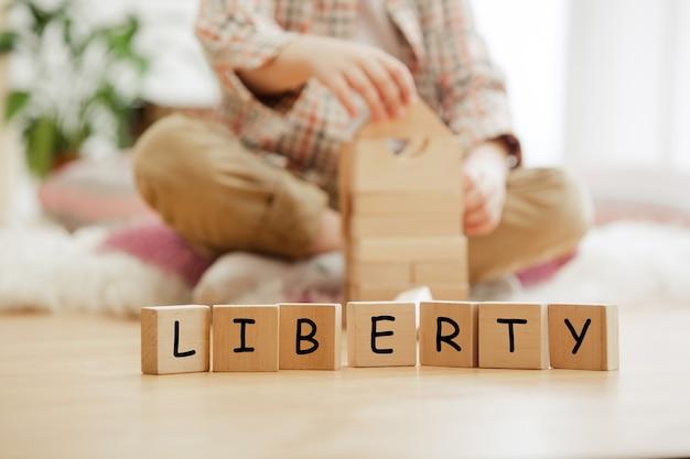 Houten kubussen met woord liberty in handen van kleine jongen thuis. conceptueel beeld over kinderrechten, onderwijs, jeugd en sociale problemen. Premium Foto