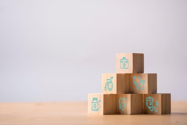 Houten kubussen stapelen van gezondheidszorg geneeskunde en ziekenhuis pictogram op tafel. zorgverzekeringen en investeringen.