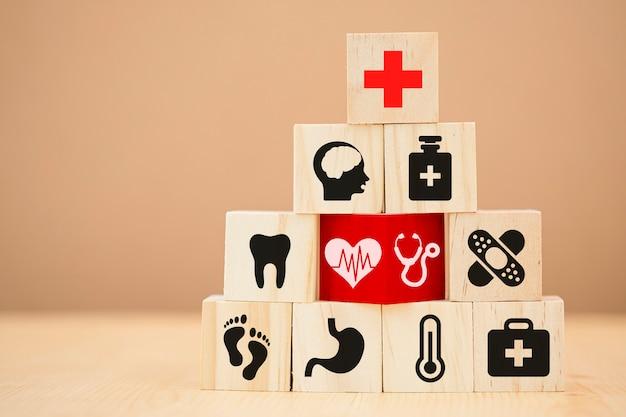 Houten kubussen stapelen van gezondheidszorg geneeskunde en ziekenhuis pictogram op tafel. zorgverzekeringsbedrijf en investeringen.