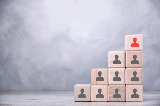 Houten kubussen worden gestapeld in de vorm van trappen op een houten tafel. het concept van ontwikkeling, de baas, de beste. met mensen, personeelspictogrammen