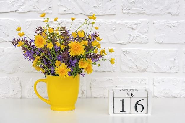 Houten kubussenkalender met datum 16 juli en gele kop met felgekleurde bloemen tegen witte bakstenen muur