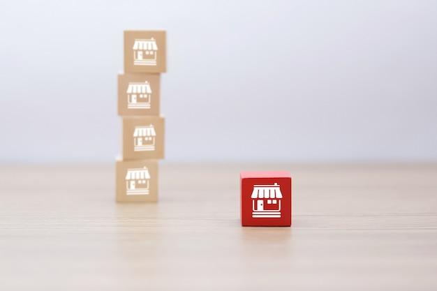 Houten kubusvorm gestapeld met franchise zakelijke pictogrammen winkel