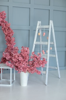 Houten ladder en slinger van eieren. decoratieve ladder en vaas met sakura in interieur