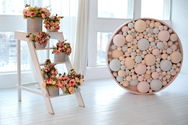 Houten ladder met boeketten pioenrozen in dozen. ladder gebruikt als planken voor verschillende planten in het interieur. bruiloft decor. kleurrijke ballen.