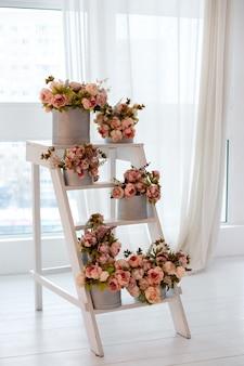 Houten ladder met boeketten pioenrozen in dozen. ladder gebruikt als planken voor verschillende planten in het interieur. bruiloft decor.