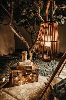 Houten lampenkap en een houten kist met boeken erop geplaatst in een tuin