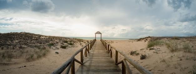 Houten lang platform dat leidt naar het strand onder de bewolkte hemel
