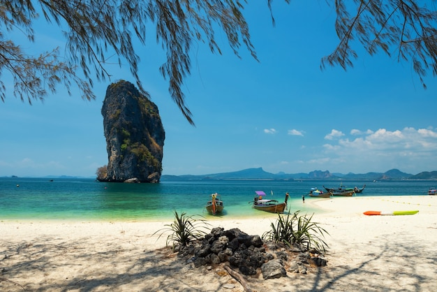 Houten lange staartboten op de turquoise andamanzee op het eiland poda met wit zand, blauwe lucht en koh poda nok in de zomer, krabi, thailand.