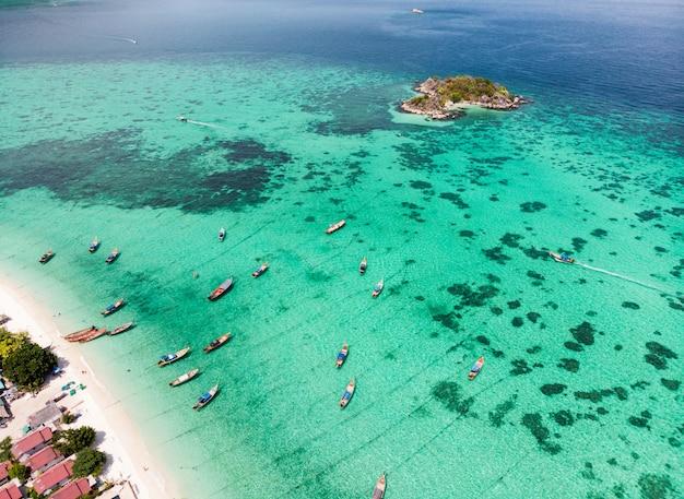 Houten langestaartboot op tropische overzees met koraalrif