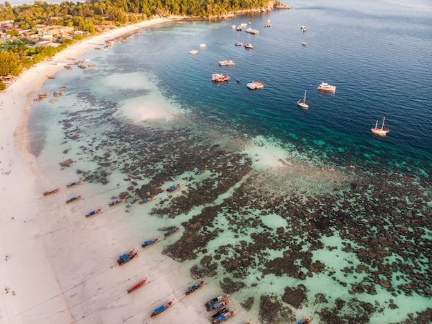 Houten langstaartboot met koraalrif op tropisch strand bij lipe-eilanden