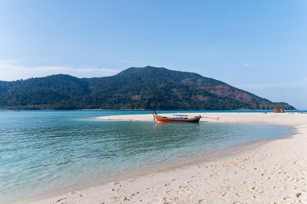 Houten langstaartboot verankerd op het strand in de tropische zee bij koh lipe, thailand