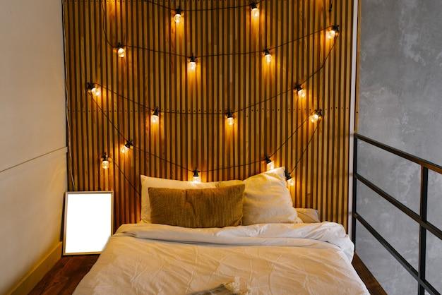 Houten latten in het hoofdeinde van het bed in scandinavische stijl. retro gloeilampen, slaapkamerverlichting
