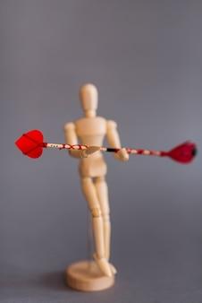 Houten ledenpop die rode liefdepijl houdt
