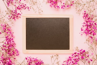 Houten lei versierd met baby's-adem bloemen op roze achtergrond