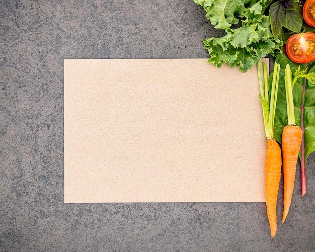 Houten lepel en groenten op donkere steenachtergrond. gezond eten en koken concept.