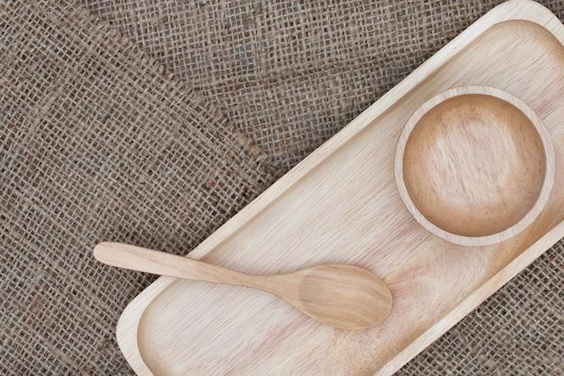 Houten lepel en houten kop die op de bruine zak wordt geplaatst.