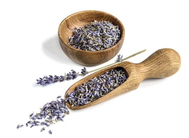Houten lepel en kom met gedroogde lavendel bloemknoppen op een witte achtergrond.