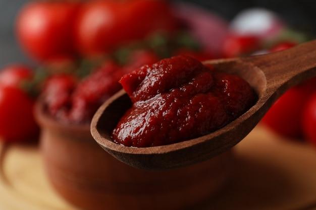Houten lepel en kom met tomatenpuree, close-up