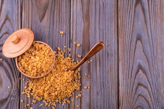 Houten lepel en kom vol bruine rietsuiker met een snufje suiker gemorst op houten tafel, bovenaanzicht
