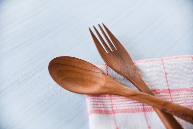 Houten lepel en vorkkeukengerei op napery op eettafel wordt geplaatst - nul afvalgebruik gebruikt minder plastic concept dat