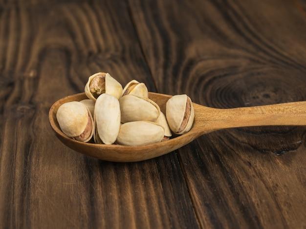Houten lepel gevuld met pistachenoten op een houten tafel. een natuurlijke bron van eiwitten en koolhydraten.
