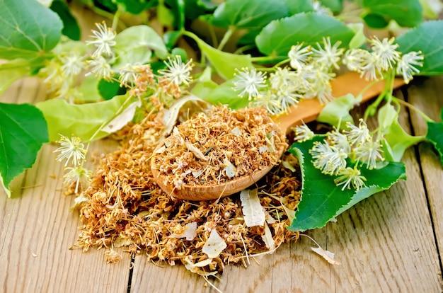 Houten lepel met gedroogde bloemen van linde, verse linde bloemen met bladeren op een achtergrond van houten planken