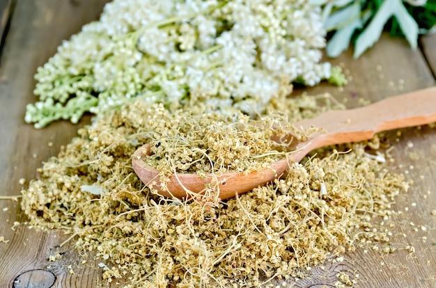 Houten lepel met gedroogde bloemen van moerasspirea op een houten plank